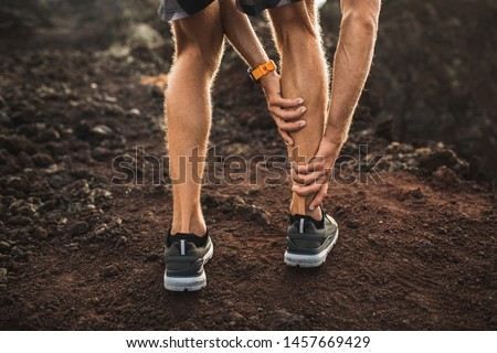 Male runner holding injured calf muscle and suffering with pain. Sprain ligament while running outdoors. View from the back close-up. #1457669429