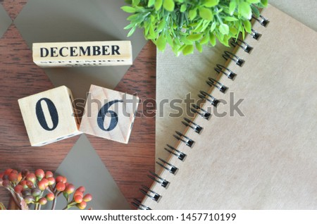 December 6. Date of December month. Number Cube with a flower and notebook on Diamond wood table for the background. #1457710199