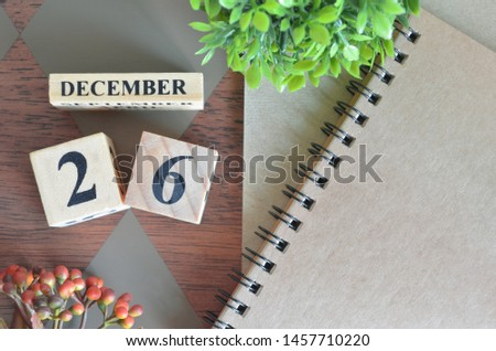 December 26. Date of December month. Number Cube with a flower and notebook on Diamond wood table for the background. #1457710220