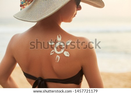 Woman With Sun Shaped Sunscreen on Her Back. Portrait Of Female With the Drawn Sun On a Shoulder #1457721179