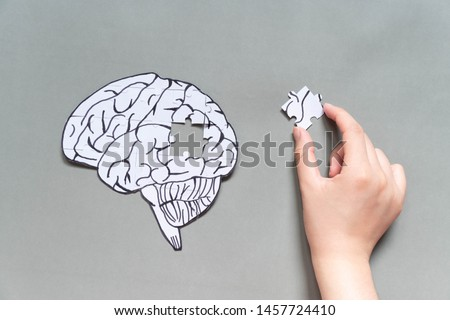 Female hand trying to connect a missing jigsaw puzzle of human brain on gray background. Creative idea for solving problem, memory loss, dementia or Alzheimer's disease concept. Mental health care. #1457724410