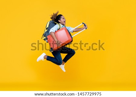 Excited African American woman tourist woman with backpack and luggage jumping in mid-air studio shot isolated on colorful yellow background #1457729975