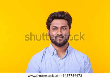 Indian handsome man wearing blue shirt on yellow background #1457739473