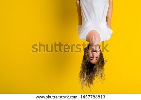 Beautiful young blonde woman jumping happy and excited hanging upside down over isolated yellow background #1457786813