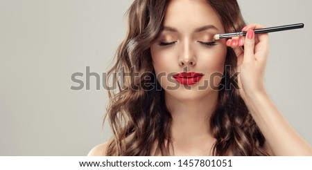 Makeup artist applies  eye shadow  . Beautiful woman face. Hand of visagiste, painting  cosmetics of young beauty  model girl . Make up in process Royalty-Free Stock Photo #1457801051