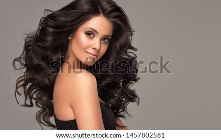 Beauty brunette girl with long  and   shiny wavy black hair .  Beautiful   woman model with curly hairstyle . Royalty-Free Stock Photo #1457802581