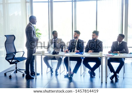 boss afro businessmen talking with arab partners colleague, multiethnic team in the office with panorama window. #1457814419