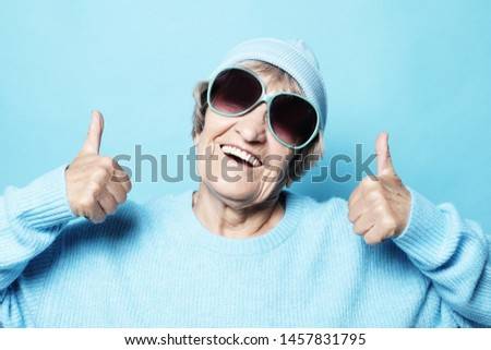 Lifestyle, emotion  and people concept: Funny old lady wearing blue sweater, hat and sunglasses showing victory sign. Isolated on blue background. #1457831795