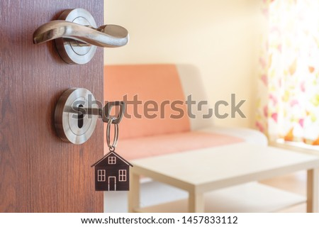 Open door to a new home. Door handle with key and home shaped keychain. Mortgage, investment, real estate, property and new home concept #1457833112