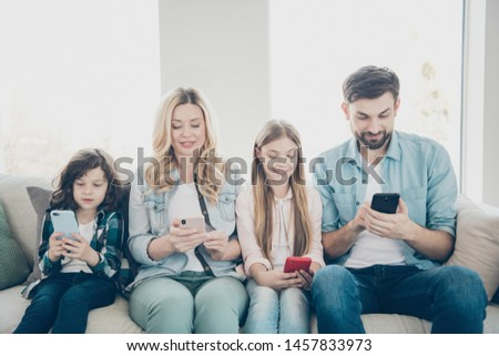 Young family two adopted children cozy sitting sofa look telephones don't care each other addiction concept #1457833973