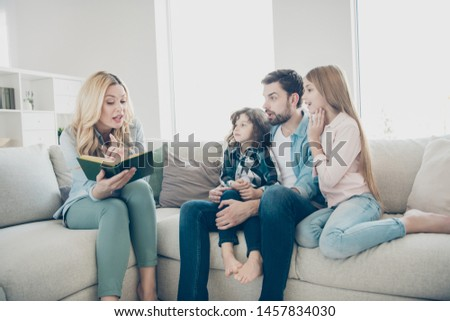 Young big family two children comfortable sitting sofa listening mommy reading exciting fairy tale #1457834030