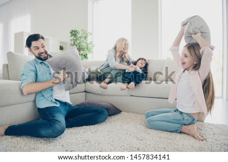 Photo of foster family four members spend leisure time rejoicing pillows fight giggle sit couch living room #1457834141