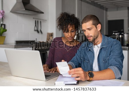 Young multiethnic couple checking bills while managing accounts on home banking app. Serious casual man and girl using laptop while looking at invoice and plan the budget to save. Royalty-Free Stock Photo #1457837633