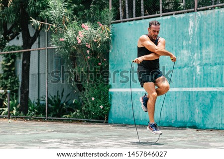 Full-length portrait of middle aged sportsman having training and doing rope jumping outdoors. Sport, fitness, street workout concept. Horizontal shot #1457846027