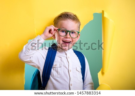 Child boy with book and bag breaking through yellow paper wall. Happy  smiling kid go back to school, kindergarten. Success, motivation, winner, genius concept. Little kid dreaming to be superhero #1457883314