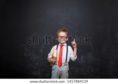 Portrait of stylish little child with finger pointed up. Little boy in glasses has idea. Kid isolated on blackboard blackboard. Success, bright idea, creative ideas and innovation technology concept. #1457884139