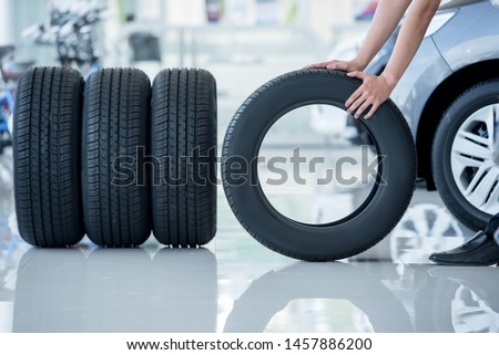 4 new tires that change tires in the auto repair service center, blurred background, the background is a new car in the stock blur for the industry, a four-wheeled tire set at a large warehouse #1457886200