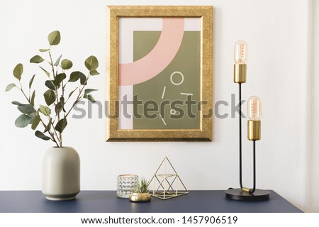 Modern and luxury interior of living room with pomegranate shelf, gold table lamp, mock up poster frame, flowers in vase and elegant accessories. Stylish home decor. Template. White walls.  Royalty-Free Stock Photo #1457906519