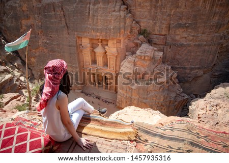 Asian woman traveler sitting on carpet viewpoint in Petra ancient city looking at the Treasury or Al-khazneh, famous travel destination of Jordan and one of seven wonders. UNESCO World Heritage site. #1457935316