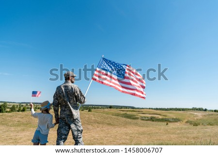 soldier holding hands with kid in straw hat and holding american flag  #1458006707