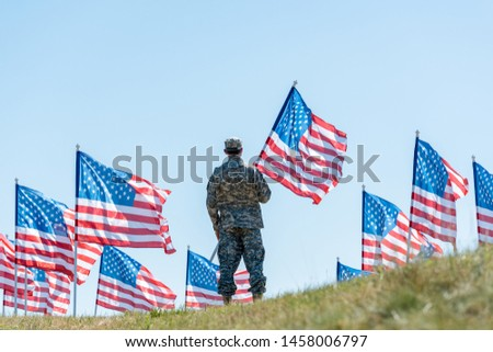 back view of soldier in military uniform and cap standing and holding american flag  #1458006797
