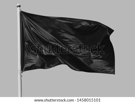 Black flag waving in the wind on flagpole, isolated on gray background, closeup Royalty-Free Stock Photo #1458015101