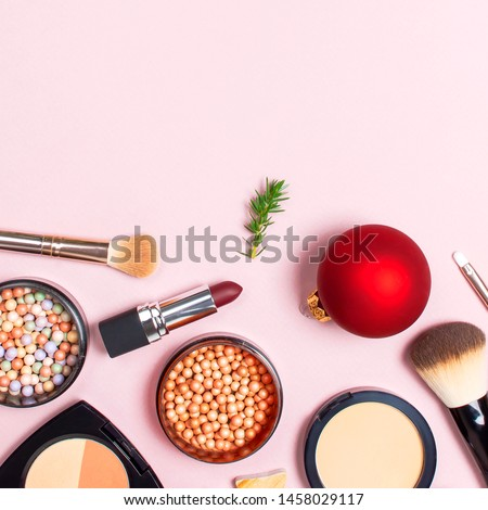Various cosmetic products for make-up, blusher, powder, brushes, lipstick, eyeshadow and Christmas gift, fir branches, red ball on pink background Flat lay top view New year concept winter decoration #1458029117