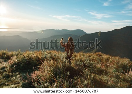 Woman standing on the mountain top using mobile phone to photograph panoramic view of mountain range in the mist under the sunrise. Travelling to the mountains