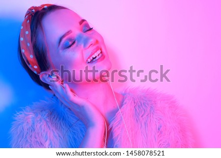 Girl in headphones listening to music. The girl smiles and laughs. Fashion portrait of young elegant girl in a pink coat and headband. Leopard print accessories. Girl dancing. #1458078521