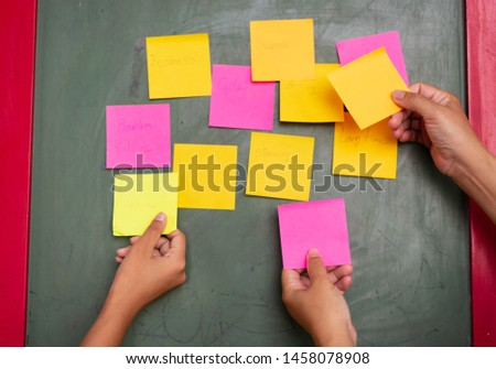 Close up woman hand holding colorful note sticky for brainstorm and share idea strategy workshop business.Brainstorming concept. #1458078908