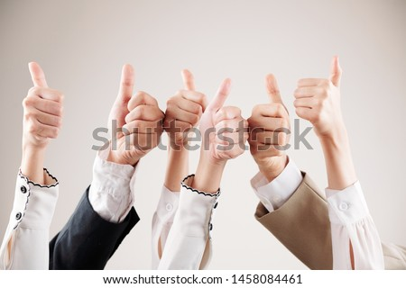 Close-up of group of business people raising their arms up and showing thumbs up isolated on white background #1458084461