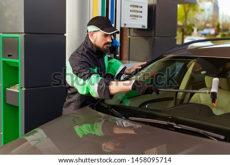 Bearded man in uniform cleaning windscreen of modern car while representing high quality service of filling station #1458095714