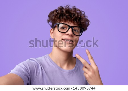 Funny nerdy youngster in glasses showing V sign and smiling while taking selfie against violet background