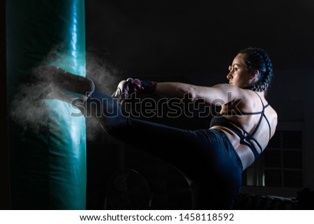 Young female boxer punching a bag on a sports training in a gym.
