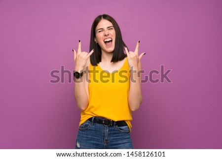 Young woman over isolated purple wall making rock gesture Royalty-Free Stock Photo #1458126101