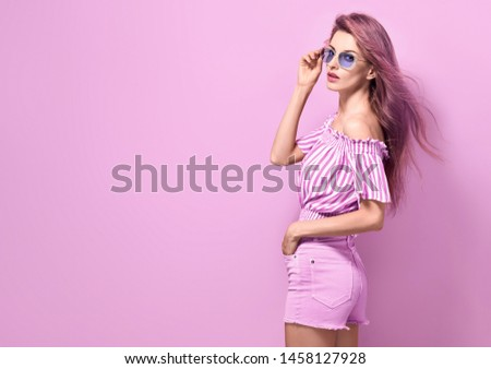 Fashion. Young Beautiful woman in Stylish romantic pink Outfit, Trendy long Hairstyle, glamour make up, Sunglasses posing in Studio. Gorgeous shapely sexy Girl in fashionable shorts on bright pink #1458127928