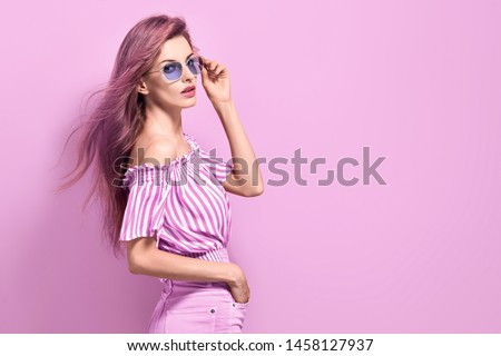 Fashion portrait Enchanting woman with trendy hairstyle, make up in stylish purple Outfit. Beautiful sensual long-haired slim model Girl in Trendy fashionable Sunglasses posing on purple. #1458127937