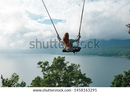 Tourist woman on a swing at vacation in Bali, Indonesia. Young girl traveler  sitting on the swing in beautiful nature place in the mountains, view on the lake #1458163295