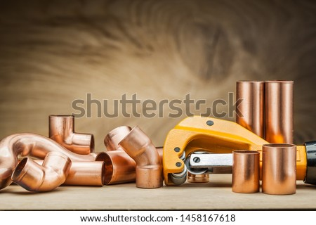 set of copper pipe fittings and  pipe cutter on vintage wood background #1458167618