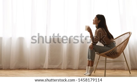Morning Relaxation. Girl Sitting in Armchair And Enjoying Coffee against Window, Free Space #1458179114