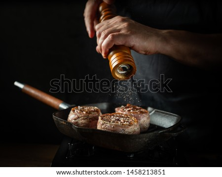 Cooking beef steak on grill pan by chef hands on black background for copy space text restaurant menu,