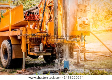 Ground water hole drilling machine installed on the old truck in Thailand. Worker keeping an eye on Ground water well drilling. Ground water well drilling. #1458220274