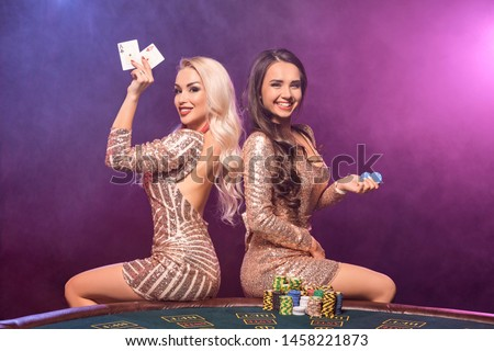Beautiful girls with a perfect hairstyles and bright make-up are posing standing at a gambling table. Casino, poker. Royalty-Free Stock Photo #1458221873