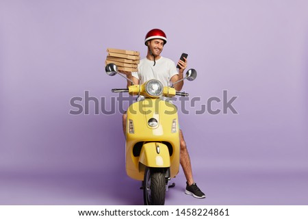 Delighted delivery man checks route via special application on mobile phone, holds paper containers with pizza, delivers fast food, wears protective helmet, rides yellow motorbike, isolated on purple #1458224861