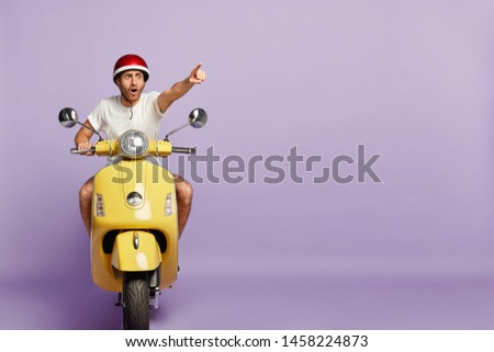 Scared man drives fast yellow scooter, wears protective helmet and white t shirt, points index finger in distance, notices scarying scene on road, poses against purple wall, blank copy space. Driving #1458224873