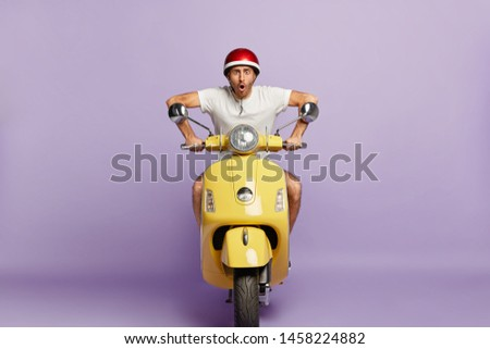 Terrified moped driver drives on high speed in helmet, stares at camera, wants to be in time, delivers something for customers, works as courier, isolated on purple background. Transportation concept #1458224882