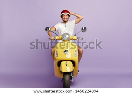 Embarrassed young guy clenches teeth, keeps hand on helmet, poses on yellow retro motorbike, forgets about driving licence, has good driving skills, enjoys free time, isolated on purple wall #1458224894