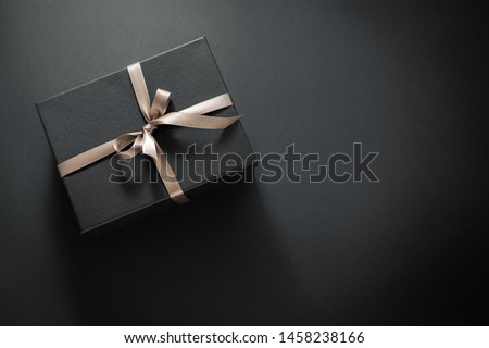 One gift wrapped in dark black paper with luxury bow on dark background. Horizontal with copy space.  #1458238166