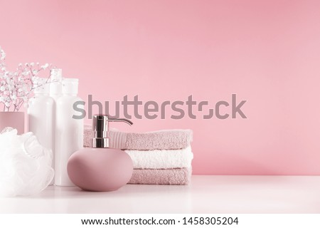 Soft light bathroom decor in pastel pink color, towel, soap dispenser, white flowers, accessories on pastel pink shelf. Elegant decor bathroom interior. #1458305204