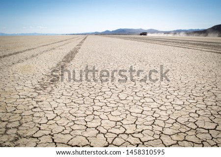Tire tracks across the Blak Rock Desert in Gerlach, Nevada and a car in the distance making a dust trail. #1458310595
